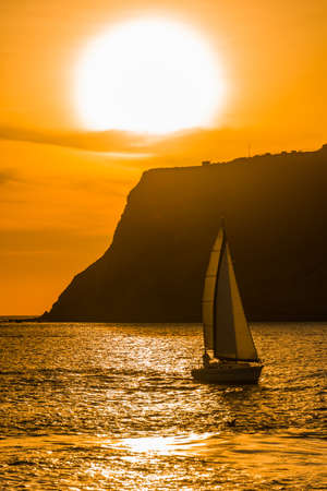 Vibrant orange ocean sunset with a sailboat sailing past a headland silhouetted against the colorful sky and reflections on the water