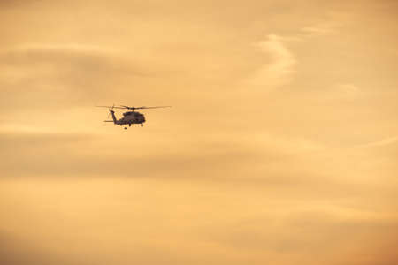 Helicopter flying against amber sky at sunset