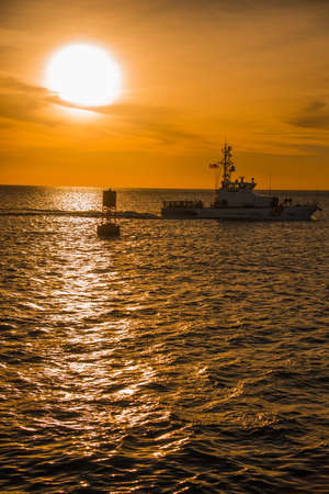Motorboat cruising past a buoy at sunset under a dramatic orange sky with the sun casting a reflection across the sea
