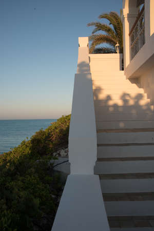 Flight of exterior steps on a luxury tropical villa in the Caribbean overlooking the ocean at sunset with a glow in the sky on the horizon and fronds of a palm tree
