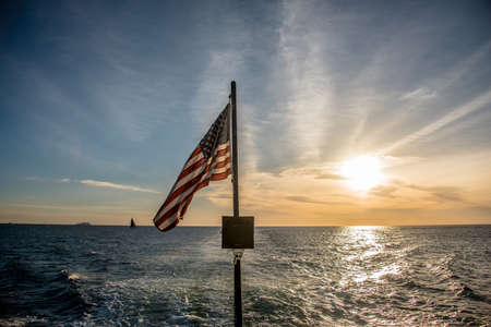 American flag flying from a sailboat at sea viewed over the stern against a sunset sky with a wake in the water behind the boat Reklamní fotografie