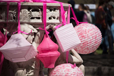 Selection of pink Chinese new Year paper lanterns of different shapes hanging by colorful ribbons form a decorative post outdoors symbolic of luck