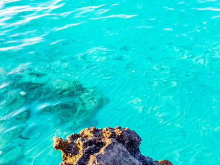 Turquoise blue clean clear water and rocks on the shoreline in Turks and Caicos Islands, Caribbean