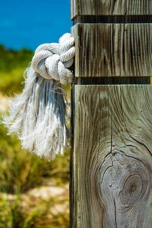 Knotted clean white rope with a frayed end protruding through a wooden post outdoors at the seaside in a close up view showing the texture of the weathered wood