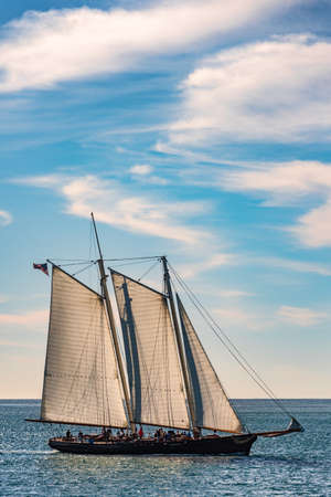 Sailboat with fully rigged sails cruising on a calm ocean under a cloudy blue sky in a side view conceptual of summer vacations Stock Photo