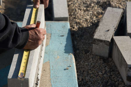 Close up view of worker measuring brick pieces with tape before laying