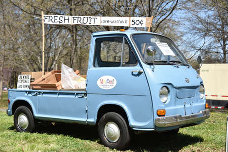 Restored blue 1960s Subaru truck used to sell fresh fruit parked on green grass with advertising signs
