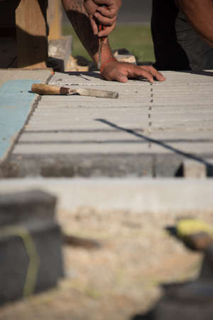 Worker using tools while laying concrete brick on sunny day