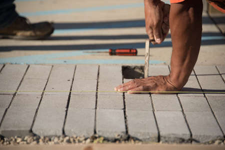 Close up view of worker laying concrete brick on sunny day
