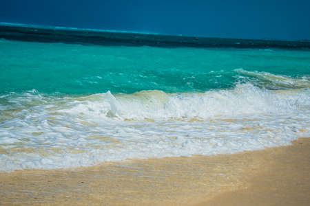 Gentle surf lapping at golden sand on an idyllic tropical beach in the Turks and Caicos Islands, Caribbean, North America