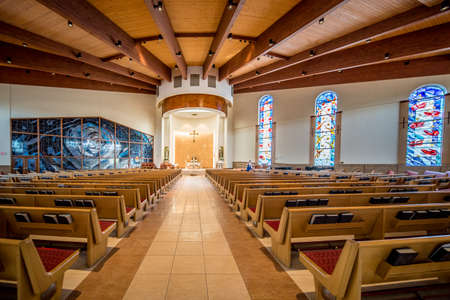 Empty catholic church with colorful stained-glass windows