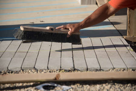 Close up view of worker sweeping concrete brick after laying on sand layer Reklamní fotografie