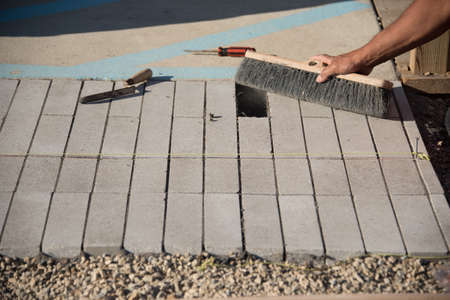 Close up view of hand cleaning concrete brick with brush