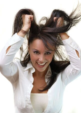 beautiful young woman pulling her hair out in a glamourous gesture and smiling to the camera