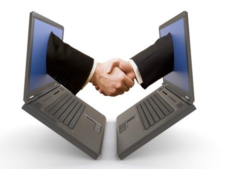 technology deal: handshake emerging from two laptop&acute,s screens. Stock Photo