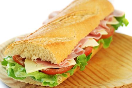 baguette: baguette sandwich with lettuce, tomatoes, ham, and cheese on a wood dish Stock Photo