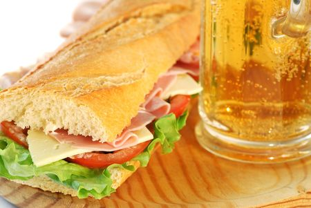 baguette sandwich closeup made of lettuce, tomatoes, ham, and cheese whit a glass of beer photo