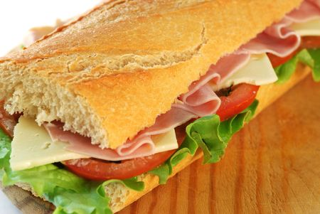 baguette sandwich closeup with lettuce, tomatoes, ham, and cheese on a wood dish
