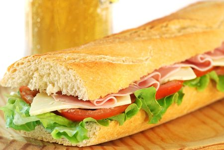 baguette sandwich with lettuce, tomatoes, ham, and cheese with a glass of beer in the background photo