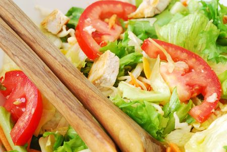 close-up view of mixed greens salad with roasted chicken in a white bowl and wooden spoons photo