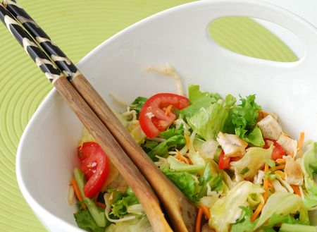 mixed greens salad with roasted chicken in a white bowl and wooden spoons photo