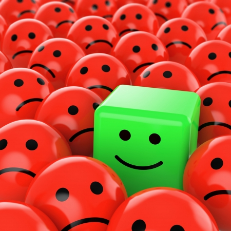 optimistic: a green happy cube smiley between many red sherical sad others as concept for unique, optimistic, positive, difference