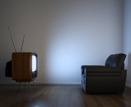copy room: Side view of retro TV and black couch in an empty white room illuminated by the screen with copy space Stock Photo