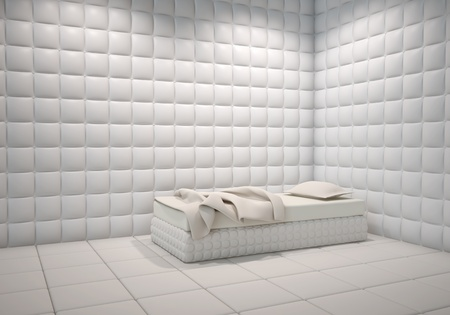 white mental hospital padded room corner with a bed photo