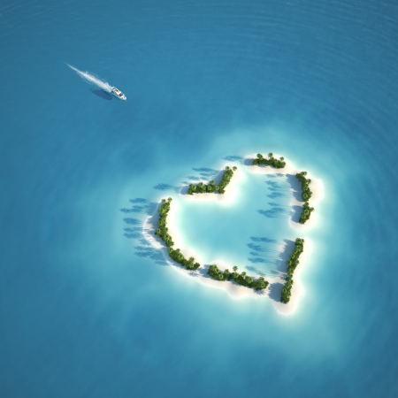 desert island: yacht heading to heart shaped island seen from the air concept for romantic vacation or valentines Stock Photo
