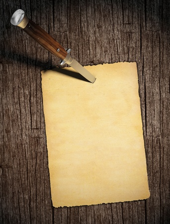 zakmes: blanck oud papier genageld aan een houten muur met een zakmes in verticale, kopie ruimte voor uw tekst