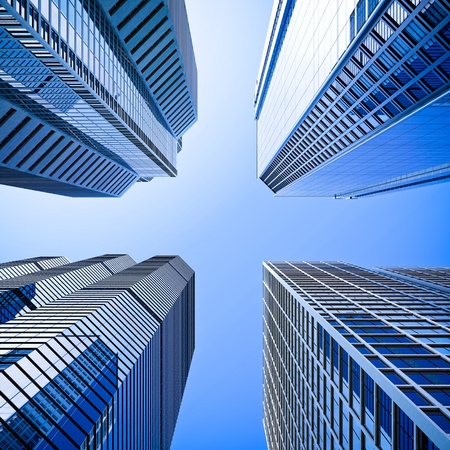 tall building: Four highrise glass skyscraper building intersection low angle shot in blue dominant against a clear sky Stock Photo
