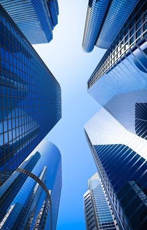 edificio corporativo: calle de edificios altos rascacielos de cristal bajo �ngulo de disparo en azul dominante contra un cielo despejado Foto de archivo