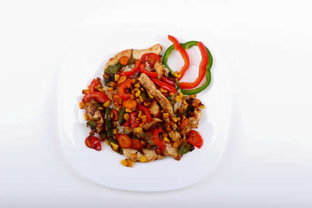 Rice with peppers and chicken on a white plate  Stock Photo