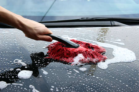Hand holding a sponge while washing car photo