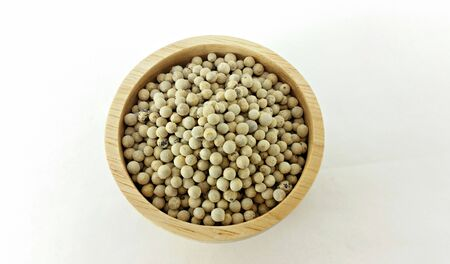 white pepper: closed up white pepper in deep wooden bowl on white background