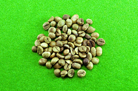 unroasted: Raw coffee beans unroasted on grass background