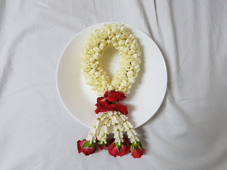 Beautiful jasmine garland with roses and crown flower  in white dish on white fablic top Stock Photo