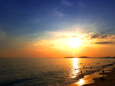 Sunset at the beach, golden sky, beautiful scene. people enjoy the beach in silhouette