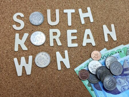 Word of South Korean Won on cork table with currency coins and bank notes