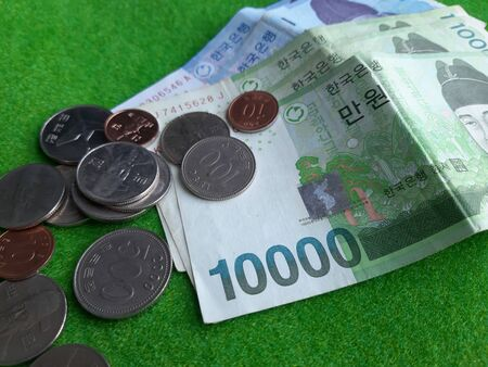 Korean coins and bank note laid on the green woolen fabric