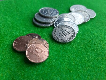 Stack of Korean coins on the green woolen fablic