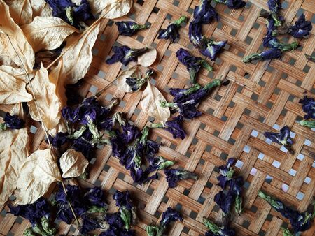 Sun dried butterfly pea flower pod and its leaves on the bamboo basket
