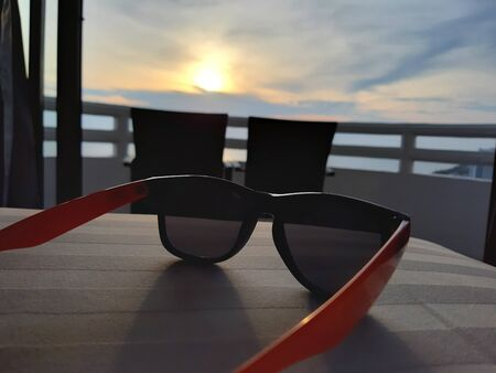 In the summer vacation. Sunglasses lay down on the hotel bed. facing to the scenic view of sunset at the balcony.