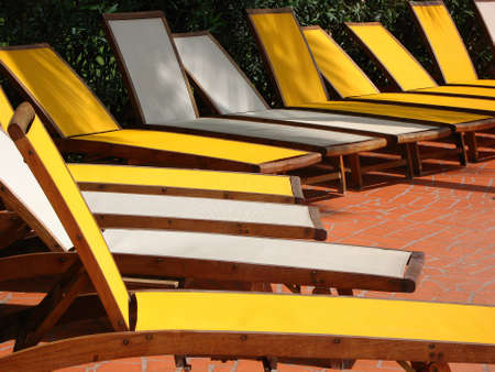 loungers: Line of empty yellow and white sun loungers Stock Photo