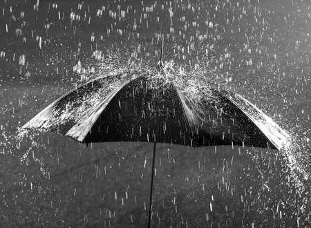 Black and white photo of umbrella in heavy rain Archivio Fotografico