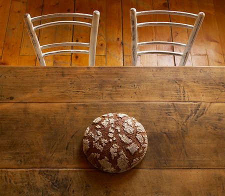 life loaf: Loaf of bread still life on brown table and two chairs