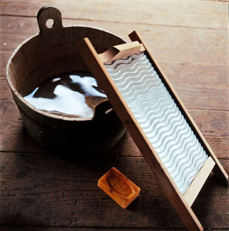 Props for old fashioned washing. Wash board, old wooden bucket of water, soap for washing clothes on wooden boards