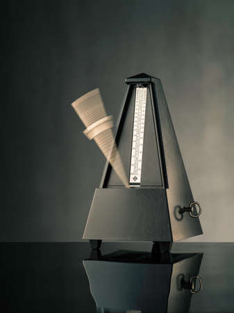 tempo: Still life photo of black metronome on grey background