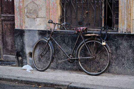 Old bicycle chained in a window in Havana