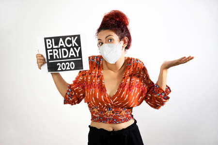 Girl with mask raising her hands and shoulders in show of resignation and conformity and holding a Black Friday 2020 poster with her hand. Young woman with white skin and curly red hair dressed in colorful patterned clothing